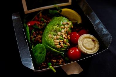 Une petite salade de lentilles accompagnée de morceaux d'avocat, de feuilles de roquette et de pignons de pain.